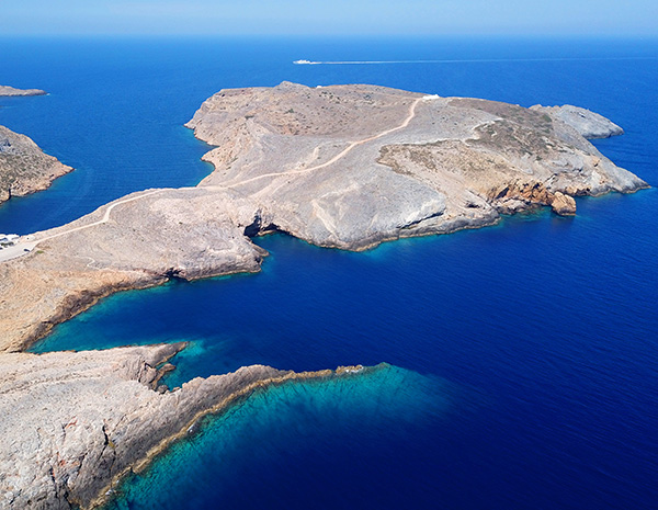 Aerial drone bird's eye view photo of picturesque bay and natural fjord of Heronisos with traditional fishing boats, taverns and clear water beach, Sifnos island, Cyclades, Greece